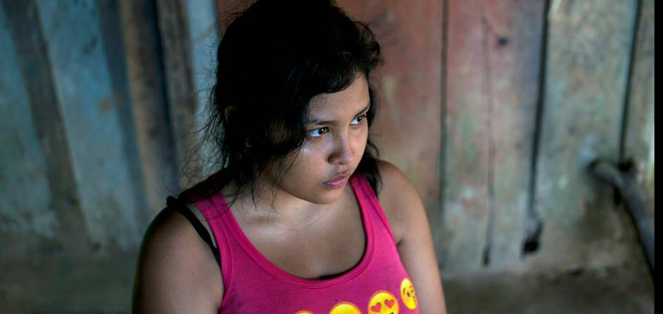 """Jackie, 17, Alexis' sister, in the family house in Omoa, Honduras on June 27th, 2016. She also wants to migrate, in spite of what happened to her brother: """"It terrifies me. It terrifies me just to think about it. But it also terrifies me to live this life, knowing there is no hope. At least I can take the risk, and have some hope."""" Alexis, his mother and five siblings live in extreme poverty, in a wood and corrugated iron shack built on a slope that turns into mud every time it rains. Alexis, mother Mercedes, and the teenage children work odd jobs when they can find them harvesting cocoa pods or chiles. Two older siblings who work and live in nearby towns help out as much as they can. Mercedes said """"Alexis had left because of poverty. He told me he was going so he could help me and all the children I have. He wanted to study."""" At the age 16, Alexis and a cousin packed their meager belongings and hit the road, hoping to escape the bitter poverty in which they grew up in Honduras. Like hundreds of thousands of others from Central America, they hoped to make it to the United States. But for Alexis, the journey ended in Mexico, when he fell off a freight train and lost his right leg - not an uncommon injury on the notorious route. Now, he is back home - a wood and corrugated iron shack built on a slope that turns into mud every time it rains. His mother and his teenage siblings work odd jobs when they can find them, harvesting chilies, taking care of other people's children or helping out in food stalls. Getting to the United States, was about more than just """"an American dream,"""" says Alexis. """"It's about getting out of the country, which has so much poverty. I wanted to get there and work and help my brothers and my mother."""" Alexis sometimes joins a local UNICEF-supported outreach group to tell other young people about the dangers of the journey. But he's convinced his own siblings will eventually try to head north. """"For the same reason I left here, my brothers and"""
