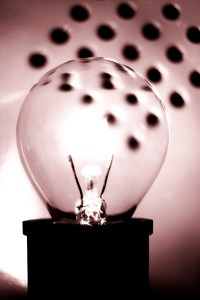 A round bulb glowing against an out of focus background. Mono sepia toned