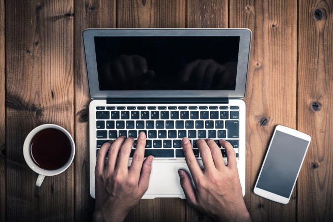 ラップトップ,ノートパソコン,木製のテーブル,俯瞰撮影,コーヒーカップとスマートフォン,タイプする男性の手