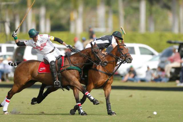 Modere's Hilario Ulloa takes the ball on the nearside as Coca-Cola's Julio Arellano rides in to defend.