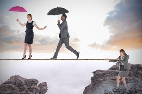 Young businesswoman pulling a tightrope for business people against rocky landscape
