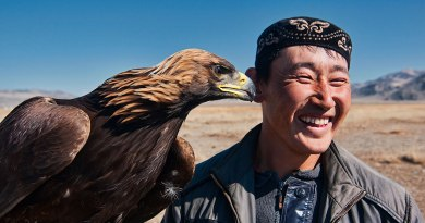Kazakh eagle hunter and his golden eagle in the Altai Region of