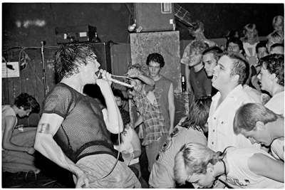 A long-haired Henry Rollins (circa 1983) sings with Black Flag in Tucson. Photo by Ed Arnaud.