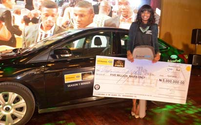 * Iroghama Ogbeifun站在她的2013 Ford Focus上,展示了她的N5万支票