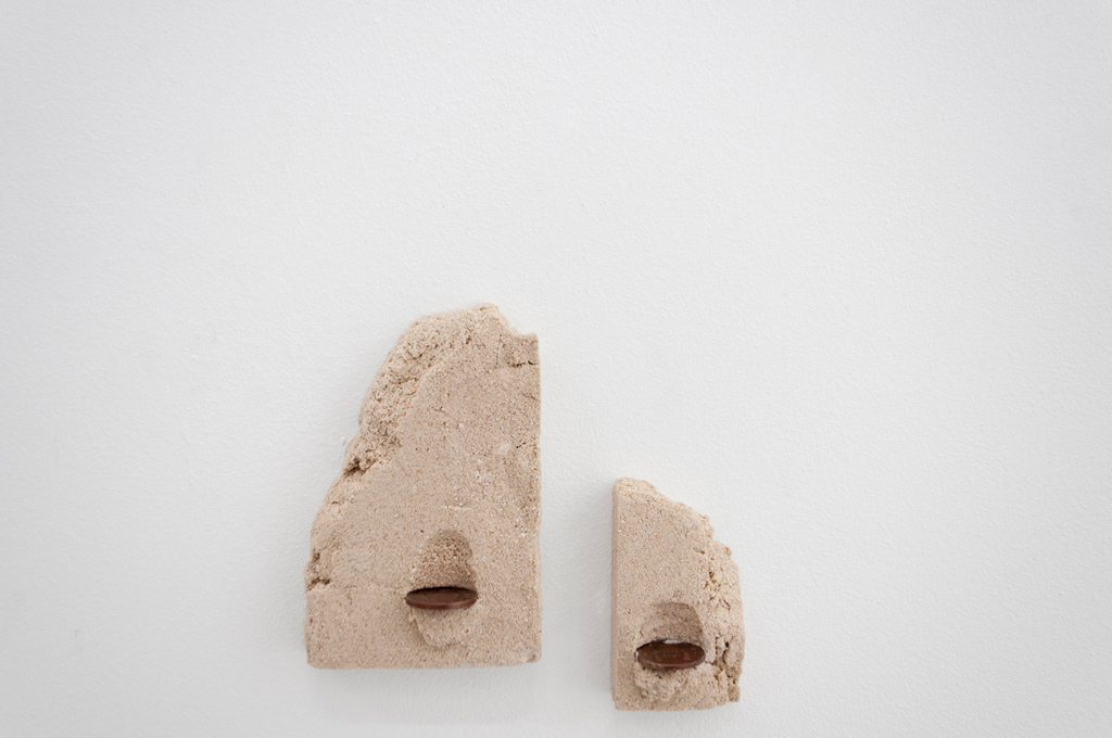 Uprights. 2015. Sand, cement, coins. 6 x 10 cm