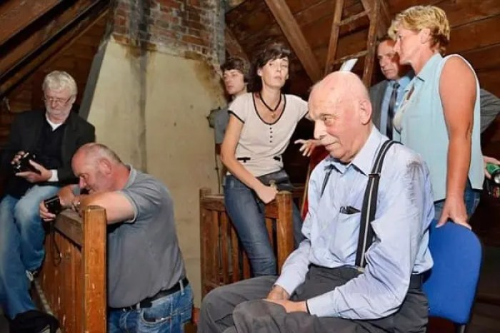 """Pic shows: Rudi Schlattner after the hiding place was revealed. This is the moment an elderly man was temporarily reunited with family property that had been hidden when he was a 13-years-old and his family were evicted in one of largest mass expulsions the world has ever seen. Rudi Schlattner was forced to flee the family casa that had been built by his merchant father after the end of World War II as part of a mass expulsion of Germans from Czechoslovakia after World War II. The destruction of World War II had caused enormous hatred in Czechoslovakia of its ethnic German population, and the government under Czechoslovak President Edvard Benes ordered the """"final solution of the German question"""" by evicting all ethnic Germans from the country. Thousands died during the forced expulsions of 1.6 million ethnic Germans their homes and into the American zone West Germany. These were the fortunate ones, and a further 800,000 were sent to the Soviet zone. Rudi and his family were among those that ended up in the American zone, and before they left they had time to hide their property in the attic of the family home. He said """"We thought we would one day return, and that would find a property there."""" Now in his 80s, he realised that this would now never happen and has now returned to make sure that even if he is not allowed to have the family property back, at least it will not be forgotten and wanted to make sure people understood who it 11 belonged to and why it was there. He contacted municipal officials in the village of Libouch in north-western Czech Republic who used the family casa now as a kindergarten, and where it was a revelation that the items had been hidden in the roof of the refurbishments carried out including the roof. But Rudi's father had done such a good job of hiding it, that nobody had discovered them. He said: """"My father built the villa in 1928 and 1929. He always thought that one day we would return and get it back."""" He was accompanied on the visit t"""