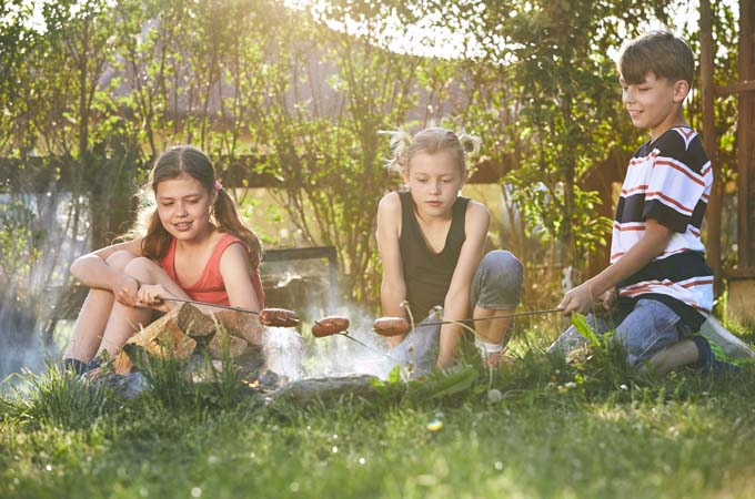 Children enjoy campfire. Siblings (family) toasting sausages on the garden at sunset.