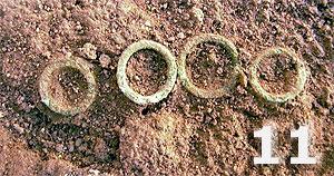 Fundstelle 424; Detailfotos der Bronzeringe, die im Brustbereich der Kinderbestattung (Bild 12) gelegen haben und ursprünglich auf dem Gewebe der Totenkleidung aufgenäht waren.