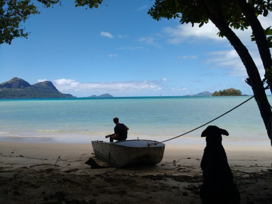 The beach on Taravai at the farm and Fatty listening to Jesse playing the guitar. Photo courtesy of Jack
