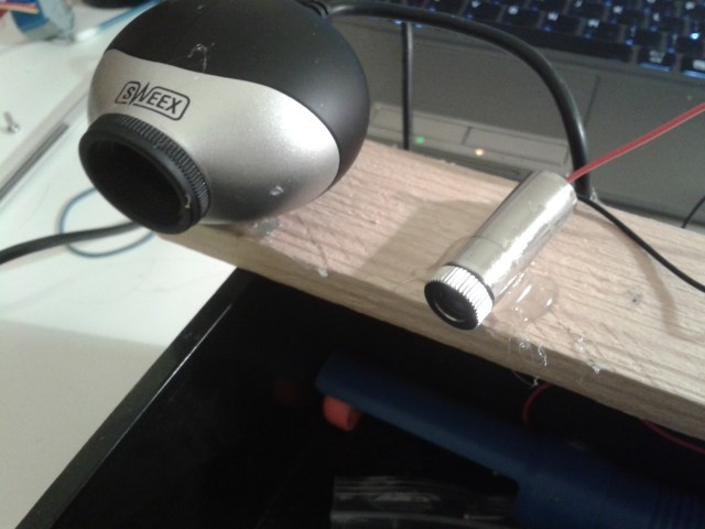 Webcam and laser hot glued to a piece of wood