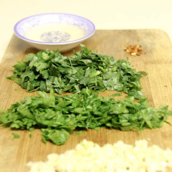 Chop Chinese parsley, flat leaf parsley, and garlic