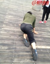 Female worker crawling on boardwalk around Ruyi Lake