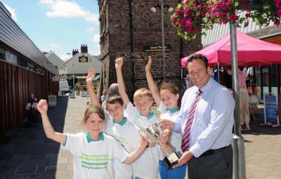 Ysgol Llangadog, the winning team of Carmarthenshire Young traders 2014 competition. Presenting the trophy is C.C.C head of co-operate property Jonathan Fearn. .Pic Jeff connell 09/07/14