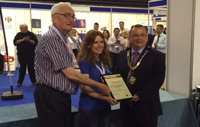 Pic caption: Cllr Jim Jones, Executive Board member for Public Protection and Trading Standards Officer Heidi Neil, accept the best local authority exhibitor award from a representative of the Chartered Trading Standards Institute.