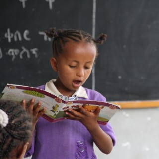 Young school girl reading storybook in front of black chalkboard, early childhood education at work
