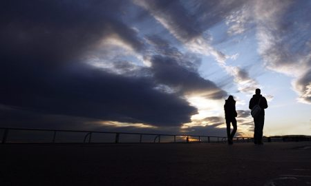 Silhouette of two people walking at sunset