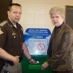 Starke County Chief Deputy Brack Rowe and Joan Haugh, Executive Director for Community Services of Starke County place unused medications in the newly-installed and secured pill drop box located at the Starke County Sheriff's Office entry.
