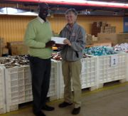 Sr. Mary Baird, PHJC, presents a check to Food Bank of Northern Indiana Executive Director Milton Lee. The money was raised during the first Empty Bowls Project at MoonTree Studios.