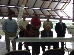 Plymouth Mayor Mark Senter (seated, right) speaks to those assembled about the airport improvements and the FAA grant