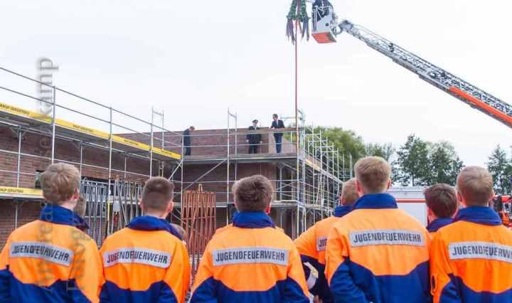 Die Jugendfeuerwehr schaut zu beim Hochhieven des Richtkranzes am neuen Feuerwehrgerätehaus in Handorf. Foto: A. Hasenkamp, Fotograf in Münster.