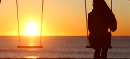 single woman on swing looking at the sunset
