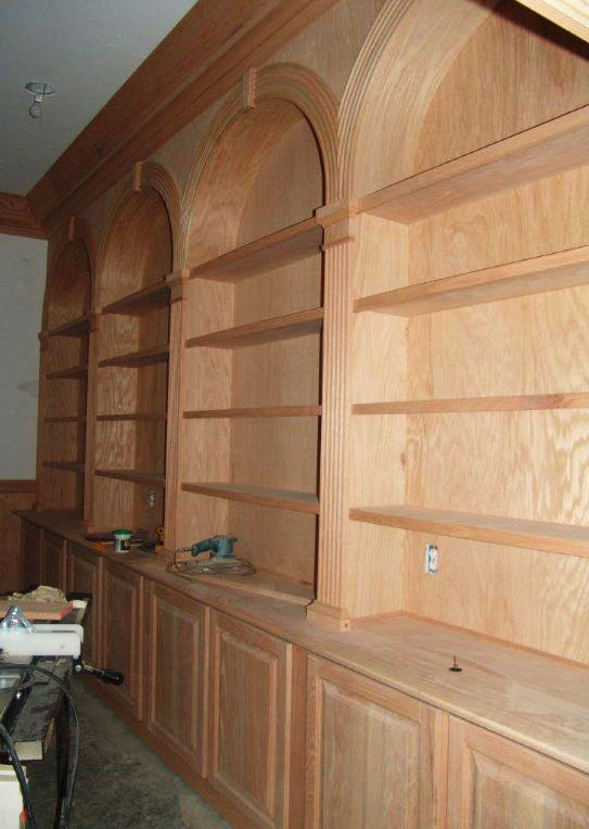 Almost done, Mike's library is a showcase of woodworking skill in red oak — raised panel doors, arched openings, crown molding, pilasters, and more.