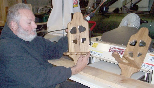 Johnny shows off a matched pair of lamp holders he's built.