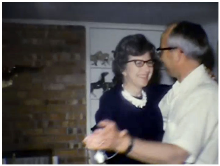 Grandparents sharing a dance in the living room. 8mm vintage film memories.