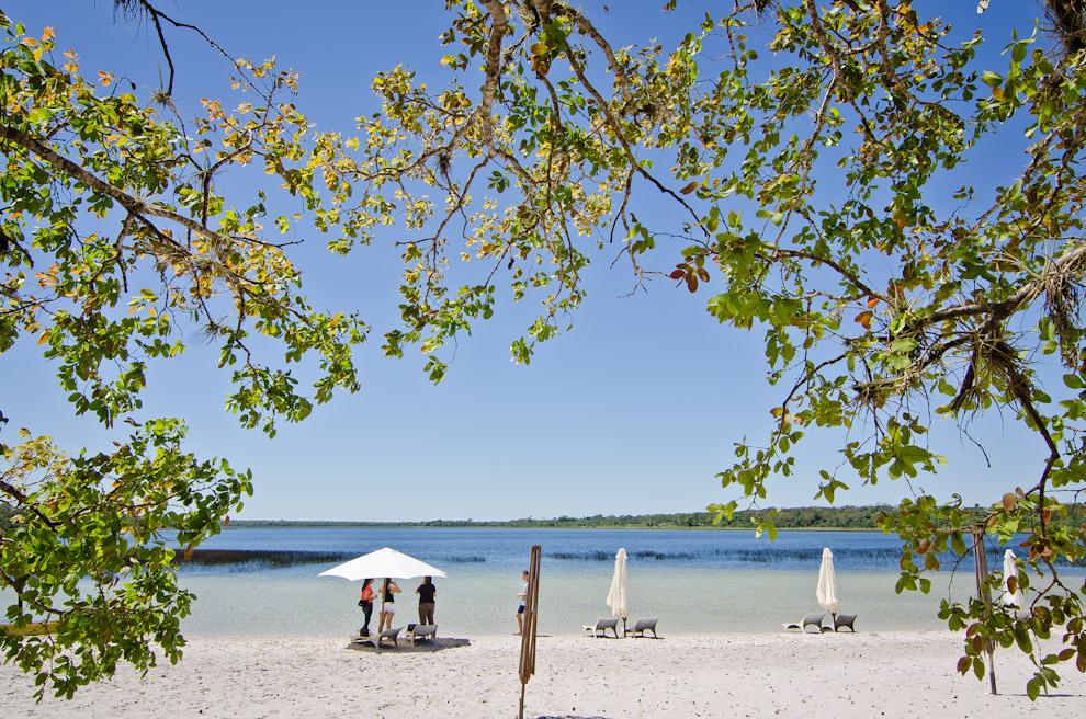 """Visitantes se deleitan con la vista de la """"Laguna Blanca"""" en la reserva natural Laguna Blanca, en el departamento de San Pedro. Cada año, este paraíso reúne a los amantes de las playas y aguas cristalinas a partir de Septiembre, mes en que el establecimiento está completamente habilitado para el veraneo. (Elton Núñez)."""