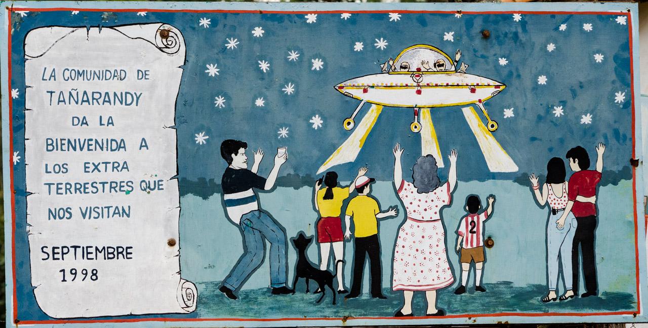 Un curioso cuadro que da la bienvenida a los extraterrestres es mostrado frente a la casa de la familia Silva, justo en frente del Yvága rape, donde se hace cada año la procesión de Tañarandy y reúne alrededor de 20 mil creyentes cada vez. El cuadro fue pintado por el artista Cecilio Thompson en 1998, hoy en día fallecido. Este y otras muestras artísticas se encuentran a lo largo del Yvága rape, en Tañarandy, de San Ignacio Misiones. (Elton Núñez)