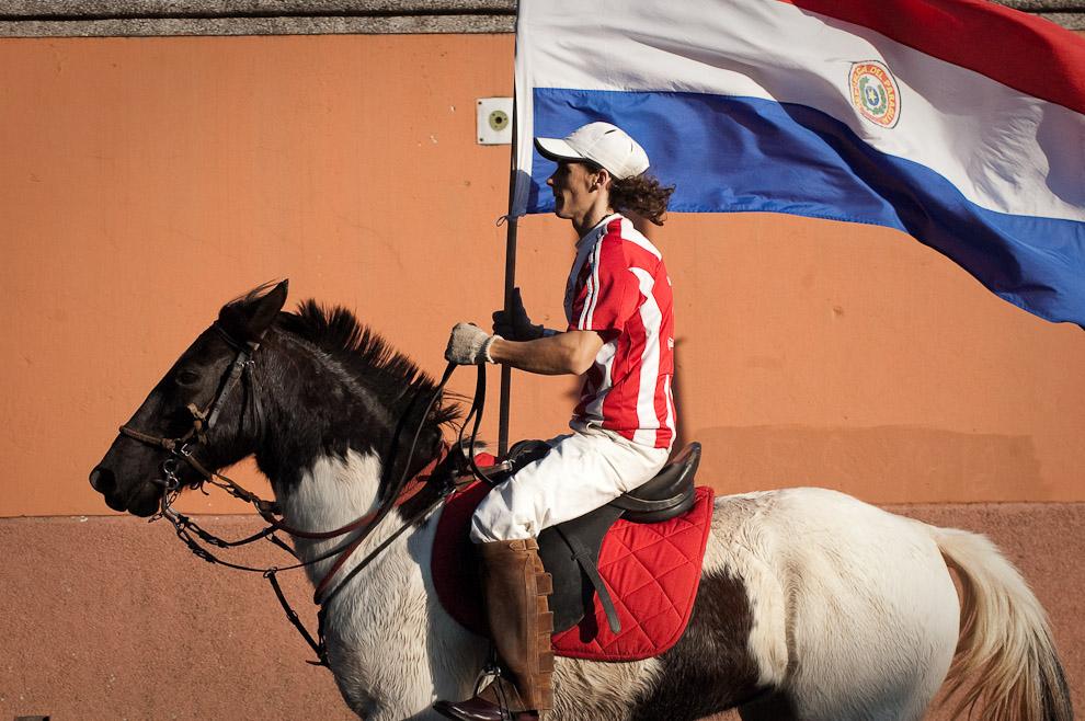 Un fanático de la Albirroja recorre las calles y la Avenida Carlos Antonio López con su caballo y la bandera Paraguaya (Elton Núñez - Asunción, Paraguay)