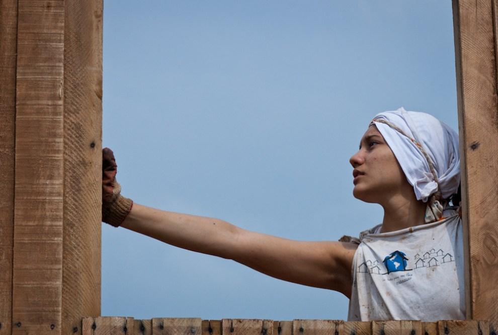 Fotografías de trabajo y solidaridad obtenidas en los 3 días de construcción de casas de emergencia con la Organización Un Techo Para mi País que fueron realizadas en el año 2010. Una voluntaria ayuda a su compañero durante la instalación de los paneles de la casa que serían las paredes una vez armados. (Elton Núñez - Asunción, Paraguay)