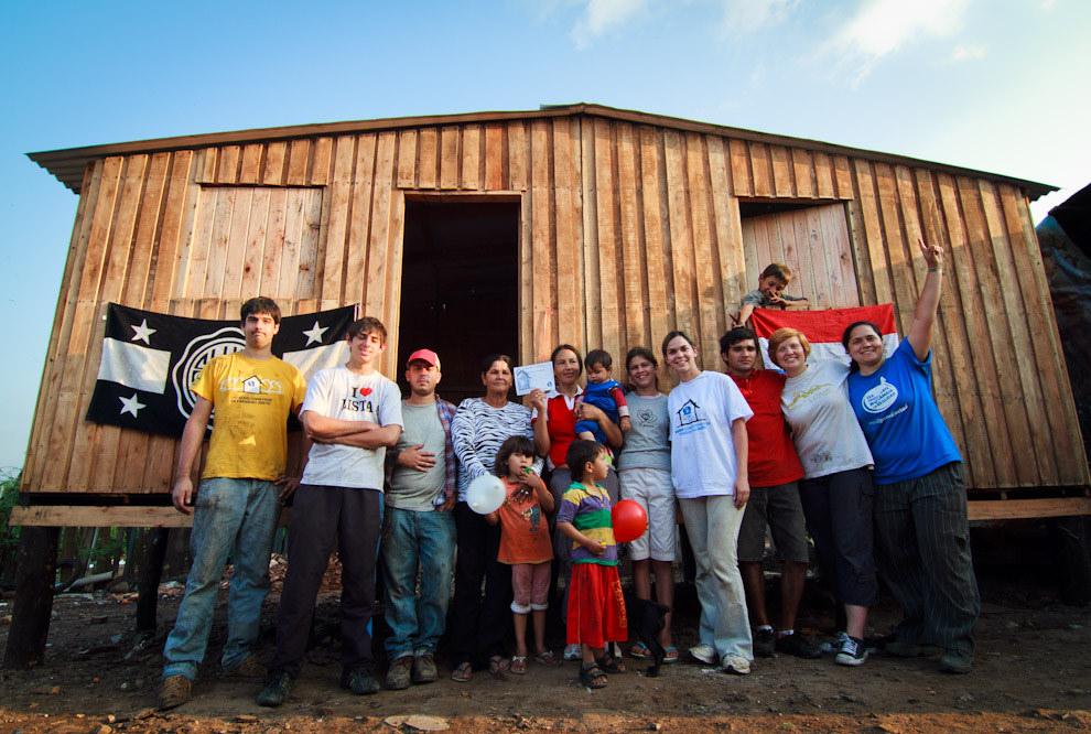 Jóvenes de la Cuadrilla posan con Doña Ignacia con su vivienda finalizada en el barrio de Yukyty - Bañado Sur (Tetsu Espósito - Lambaré, Paraguay)