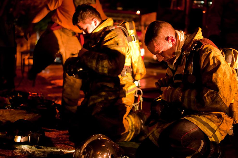 Un bombero francés se desprende la mochila de respiración autónoma de la misma forma que su colega paraguayo, respetando los procedimientos de la casa, al término de un servicio codificado como incendio de edificio de mediana magnitud. El bombero francés pertenece a un grupo de instructores de un curso avanzado de rescate de altura que había venido para entrenar a los bomberos de la 3ra. compañía. Sin embargo, honrando su código, un bombero es un bombero en cualquier parte, se ofreció para entrar al incendio con los demás voluntarios paraguayos. (Elton Núñez).