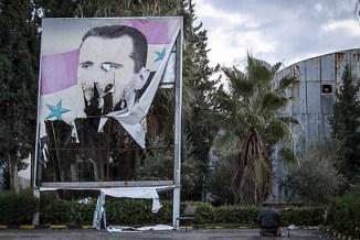 בדרך החוצה? כרזה קרועה של אסד בעיר חלב (צילום: AP)
