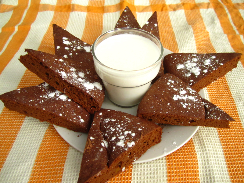 Triangle slices of brownies on plate in star shape with glass of milk