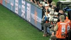 Fotógrafos empoleirados em torno do painel publicitário