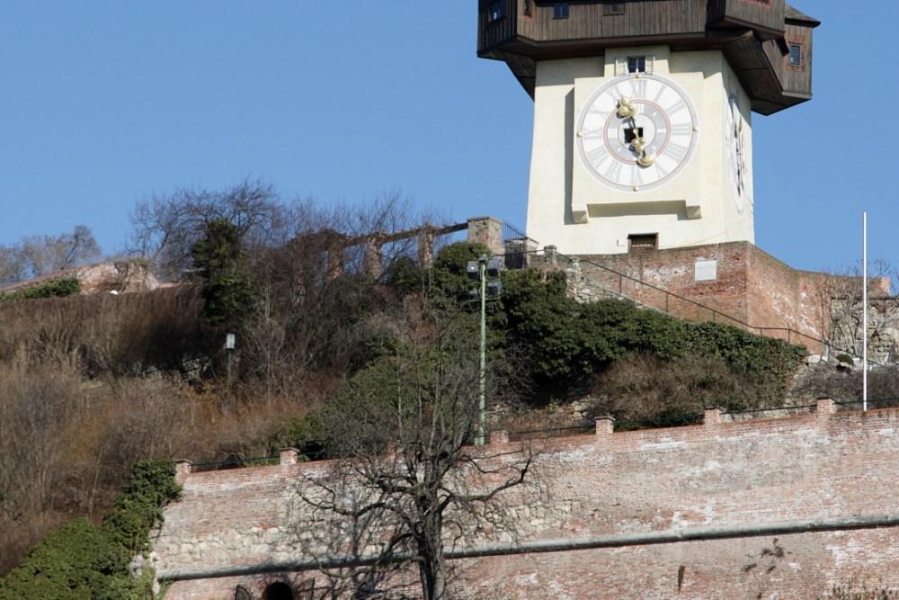 """Der Grazer Uhrturm gilt als Wahrzeichen von Graz. Er ist 28 Meter hoch und einer der letzen Überreste der Grazer Burg, einer mächtigen Wehranlage die nach der Besetzung Wiens 1809 durch Napoleon geschliffen werden mußte. Der Glockenturm und der Uhrturm wurden von den Grazern freigekauft und somit vor der Zerstörung bewahrt.  Der Kern des Grazer Uhrturms wurde wahrscheinlich im 13.Jahrhundert errichtet. Erste Nennungen des Turms finden sich um 1265, allerdings wurde der Uhrturm erst 1560 in seiner heutigen Form fertig gestellt. Vier große Zifferblätter (Durchmesser mehr als fünf Meter), die aus dem Jahr 1712 stammen, schmücken die vier Seiten des Turms.  Ursprünglich verfügte die Uhr des Turms lediglich über einen großen Stundenzeiger, der zur besseren Ablesbarkeit aus größerer Entfernung beitrug. Um den später installierten Minutenzeiger vom Stundenzeiger unterscheiden zu können, musste dieser daher kleiner gestaltet werden. Deshalb sind die vergoldeten Zeiger auch heute noch in der Größe vertauscht.  Heute sind im Turm noch drei Glocken erhalten: Die Stundenglocke; sie ist laut ihrer Inschrift die älteste von Graz (1382) und schlägt zu jeder vollen Stunde. Die Feuerglocke (1645); sie warnte vor Feuern. Die Armensünderglocke (ca. 1450): sie läutete ursprünglich zu Hinrichtungen; im 19. Jahrhundert aber zur Sperrstunde, was ihr zusätzlich den Namen """"Lumpenglocke"""" eintrug."""