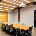 Large employee conference room.  Glass doors open up the space to the commons area and stained plywood creates an anchoring wall/ceiling system