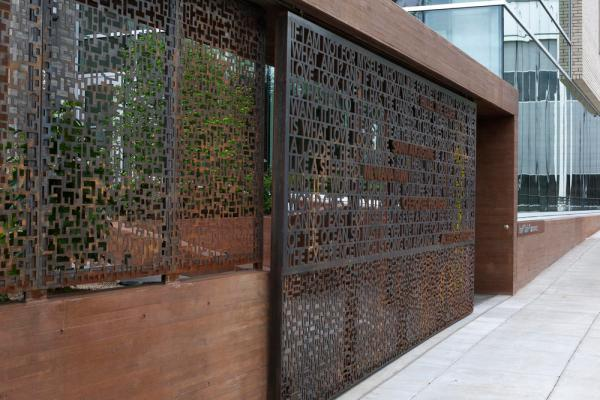 View of custom entrance gate, featuring inspirational quotes on recycled weathering steel. - Photo Credit: Sally Schoolmaster
