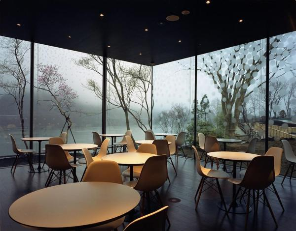 the cafė with etched glass overlooks the lake, Image Courtesy © Christoffer Rudquist