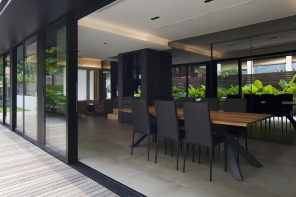Reflective surfaces within the interiors strive to bring the greenery from the adjacent decked terrace into the living spaces., Image Courtesy © BETON BRUT