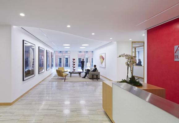 The bright reception area incorporates contemporary artwork and framed views of the streetscape, Image Courtesy © Paul Riddle