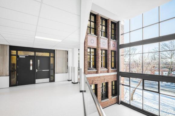 Full-height glazed atrium highlights one of the older brick facades, Image Courtesy © Charles Lanteigne