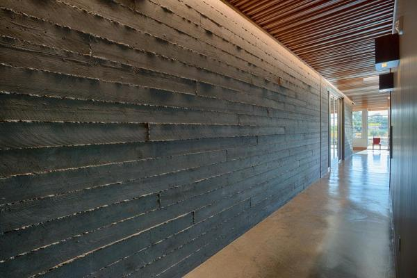 The concrete board-form walls that from the exterior façade continue at the interior and provide a textured surface for a recessed LED light above.  Matching interior and exterior finish materials allowed for a blending between the two spaces,  Image Courtesy © Technical Imagery Studios