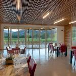 The suspending ceiling of the Hospitality Room is comprised of long horizontal slats of varied widths and depths with a view of the surrounding vineyards through bi-fold Nana Walls.  Glass blade LED light fixtures hang between the slats in a staggered composition.  The slatted ceiling mitigates acoustical resonance and allows for flexible ventilation,  Image Courtesy © Technical Imagery Studios