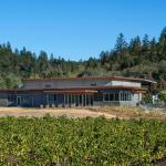 The west façade of Titus Winery is characterized by the covered Hospitality area overlooking surrounding vineyards.  Exterior materials include cedar soffits, concrete board-form tilt-up walls, gunmetal blue panels above windows, and anodized aluminum window frames,  Image Courtesy © Technical Imagery Studios