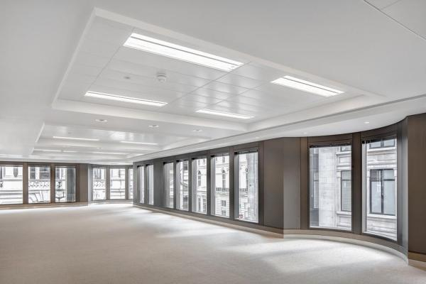 Combined with the renewal of the lighting, this physically and visually increases the floor height, whilst providing a well lit and tempered prime office space, Image Courtesy © Jan Piotrowicz