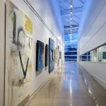 The art gallery and boat storage spaces are placed side by side to illustrate their connection.  Track lighting and blue atmospheric lighting create universal space, Image Courtesy © Gray City Studios (Scott McDonald)