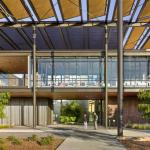 The entrance features an expansive photovoltaic (PV) trellis that provides shade and cover, and more electricity than needed to power the facility. It serves as an organizing and unifying architectural element throughout, Image Courtesy © Robert Canfield